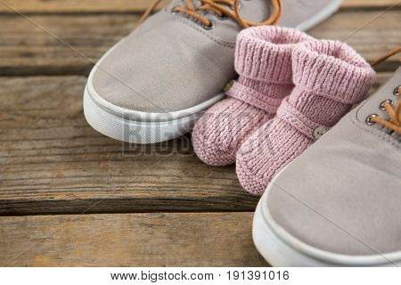 Close up of shoes and baby booties on wooden table