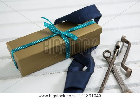 Close up of gift box with necktie by hand tools on white table