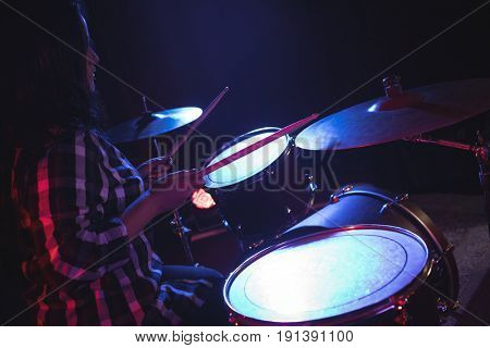 Side view of female drummer practicing in nightclub