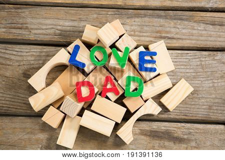 High angle view of love dad text on wooden blocks at table