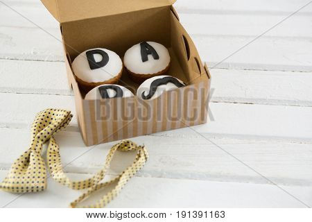 High angle view of cupcakes with text in box by bow tie on white table
