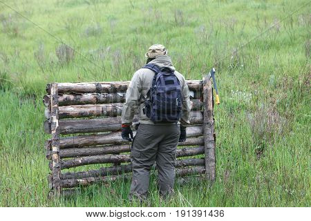 Male traveler with an ax and a backpack on a background of green mountains and firewood