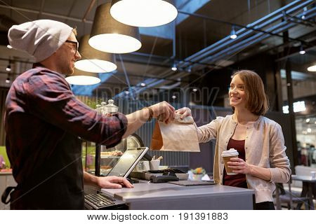 small business, food, people and service concept - happy female customer with coffee cup taking paper bag from man or barman at vegan cafe