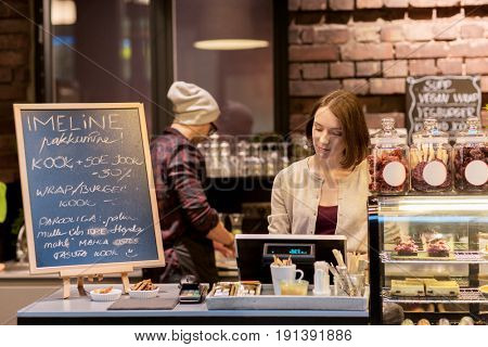 small business, people and service concept - woman or bartender at cafe or coffee shop counter with cashbox and menu