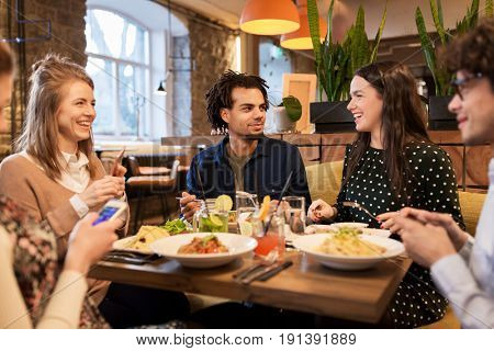 leisure, food, drinks, people and holidays concept - happy friends with smartphones eating and drinking at restaurant