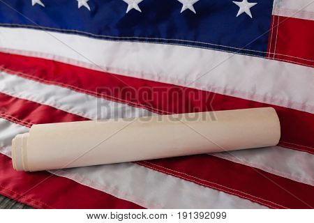 Close-up of rolled-up document arranged on American flag
