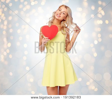 love, valentines day and people concept - smiling young woman in dress with red paper heart over holidays lights background