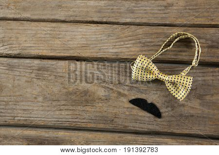High angle view of mustache with bow tie on wooden table
