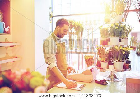 people, sale, retail, business and floristry concept - happy smiling florist man with clipboard and cashbox writing and making notes order at flower shop counter