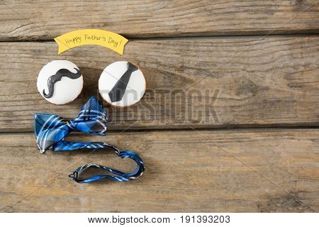 Overhead view of cupcakes with bow tie on wooden table