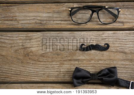 High angle view of mustache with eyeglasses and bow tie on wooden table