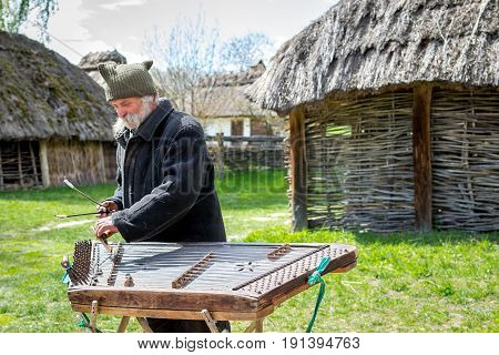 Kyiv Ukraine - April 23 2017: An elderly Ukrainian man a peasant with a long mustache and beard plays an ancient musical instrument of cymbals. Vintage village with wooden houses. Museum Pyrohiv