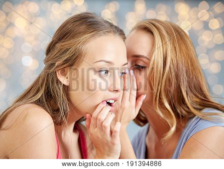 friendship, people and communication concept - happy young women gossiping and whispering to ear over lights background