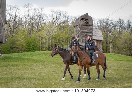 Kyiv Ukraine - April 23 2017: Policemen on horseback a beautiful spring landscape mounted police horsemen in the countryside outdoors. National Museum Pirogovo in the outdoors near Kiev.