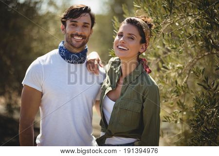 Portrait of cheerful young couple standing by trees at farm