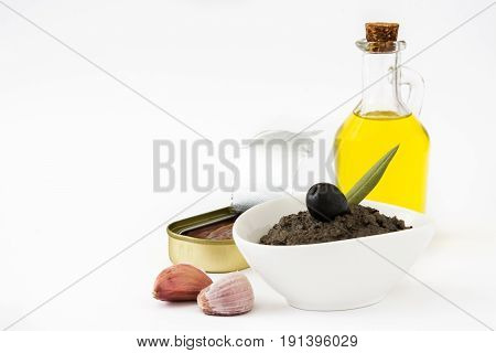 Black olive tapenade with anchovies, garlic and olive oil isolated on white background