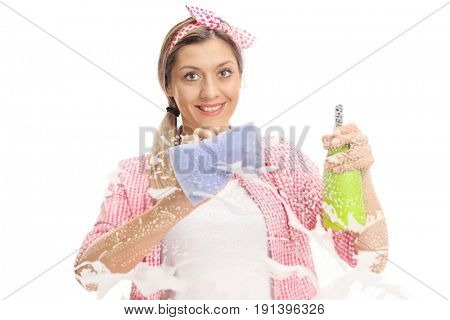Young woman cleaning a window with a towel and a detergent isolated on white background