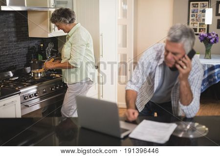 Senior man talking on phone while wife cooking in kitchen at home