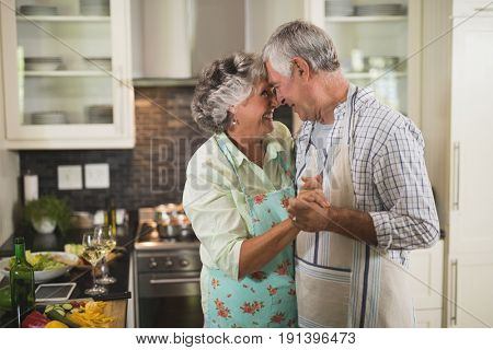 Smiling senior couple dancing in kitchen at home