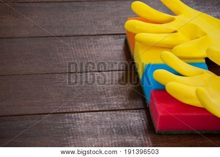 Close-up of yellow gloves with scouring pad on a wooden floor