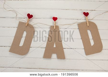 Dad text with cloth pegs hanging on rope against wooden background