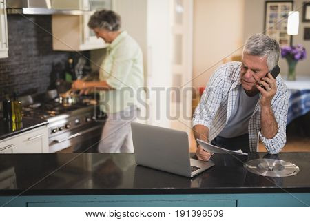 Senior man talking on phone while woman cooking in kitchen at home