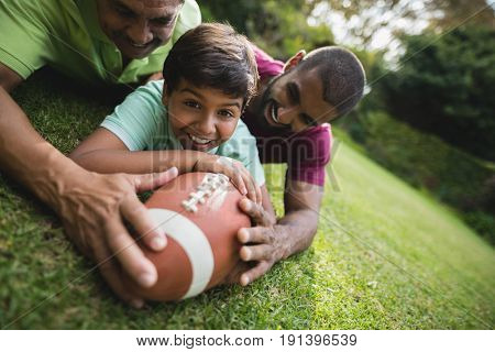 Portrait of happy boy playing rugby with father and grandfather at park