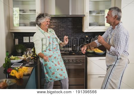 Active senior couple dancing in kitchen at home