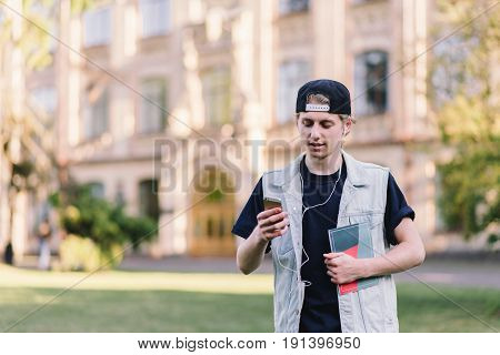 A stylish, interested student in a cap wears a mobile phone and listens to music at the background of the university. On campus background. Student Life.