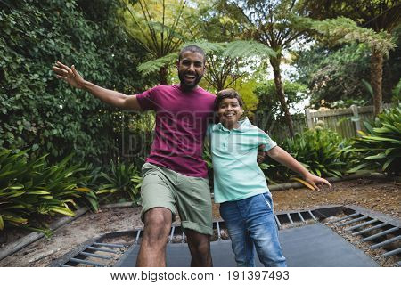 Portrait of happy father and son jumping on trampoline at park