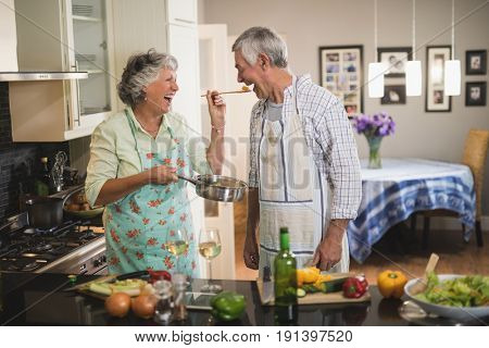 Cheerful senior woman feeding man in kitchen at home