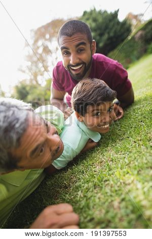 Happy multi generation family lying on grass at park