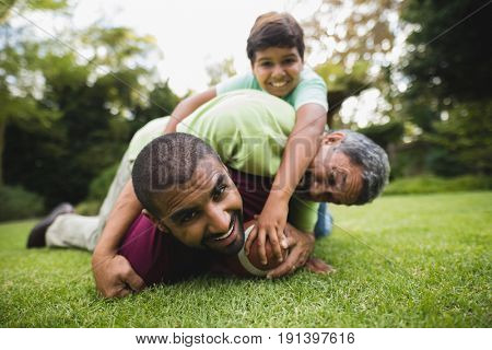 Portrait of happy multi generation family playing rugby at park