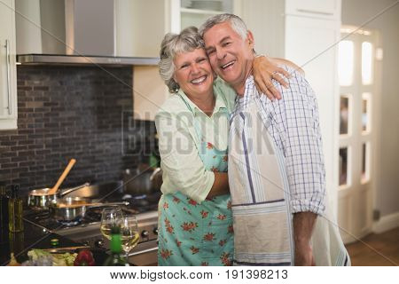 Portrait of smiling senior couple embracing in kitchen at home