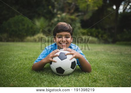 Portrait of smiling boy with soccer ball lying on field at park