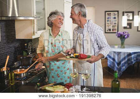 Happy senior couple looking at each other preparing food together in kitchen at home