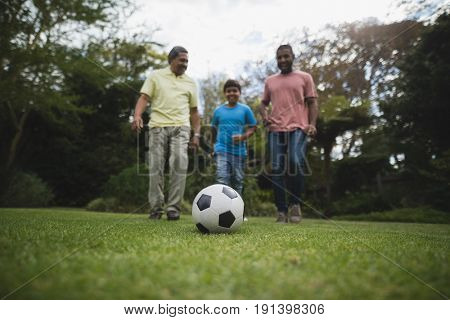Multi-generation family playing soccer together on field at park