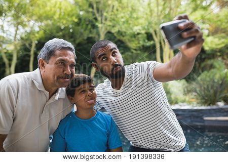 Happy multi-generation family making faces while taking selfie together at park