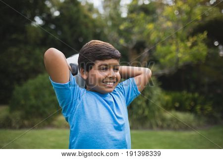 Smiling boy holding soccer ball behind head at park