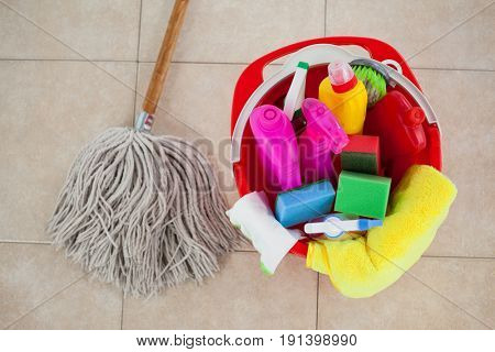 Close-up of bucket with cleaning supplies and mop on tile floor
