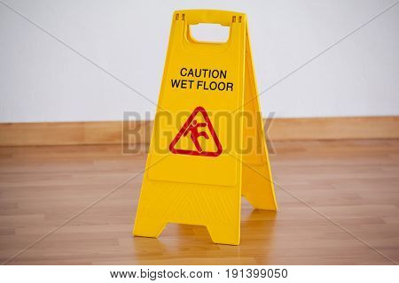 Close-up of wet floor caution sign on wooden floor