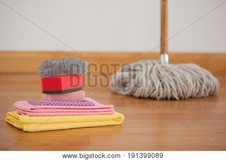 Close-up of mop and cleaning equipment on wooden floor