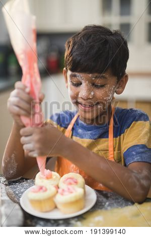 Boy making cup cakes in kitchen at home