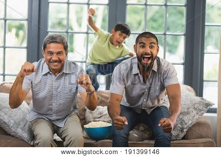 Cheerful multi-generation family watching television together at home