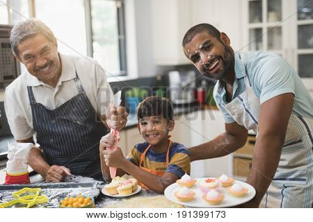 Portrait of happy multi-generation family preparing sweet food together in kitchen at home