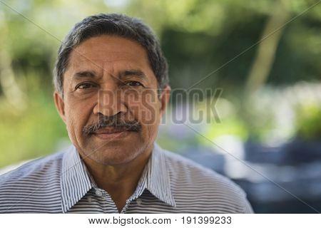 Portrait of serious senior man at porch