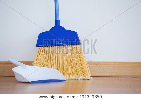 Close-up of dustpan and sweeping broom on wooden floor