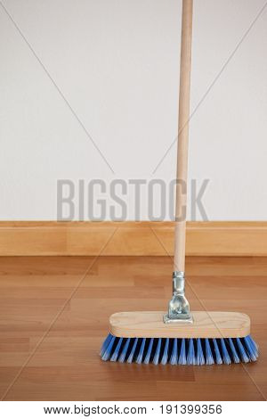 Sweeping broom with wooden handle on floor against wall