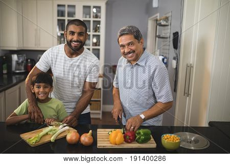 Portrait of happy multi-generation family preparing food together in kitchen at home