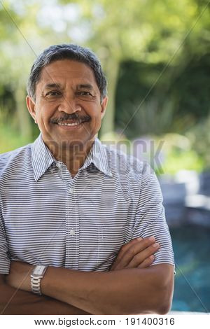 Portrait of smiling senior man with arms crossed standing at porch